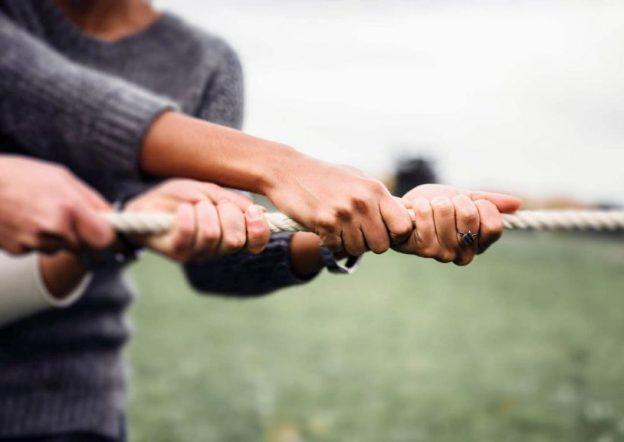 las manos de una mujer y un hombre en primer plano tiran de una cuerda blanca que está tensa