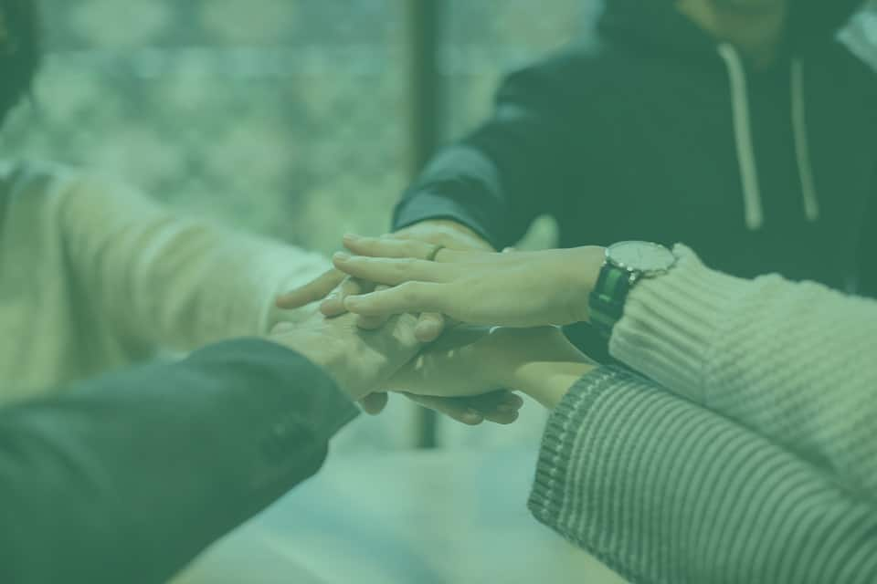 Imagen de manos una sobre otra representando el trabajo en equipo