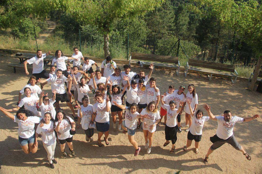 Fotografia aéria d'un grup de nois, noies i monitors del projecte Vitamina a un parc, tots porten una samarreta blanca del projecte i saluden a la càmera