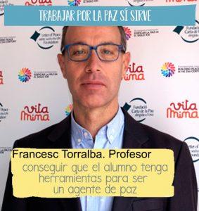 """Fotografía de Francesc Torralba, profesor del postgrado de cultura de la paz delante de un fotocall del projecto Vitamina, hay una cita sobreimpresa """"conseguir que el alumno tenga herramientas para ser una agente de paz"""""""