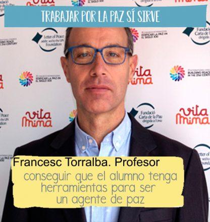 Fotografía de Francesc Torralba, profesor del postgrado de cultura de la paz delante de un fotocall del projecto Vitamina, hay una cita sobreimpresa