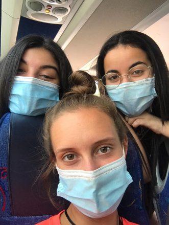 Primer plànol de tres noies del projecte Vitamina a un autocar, totes porten mascareta
