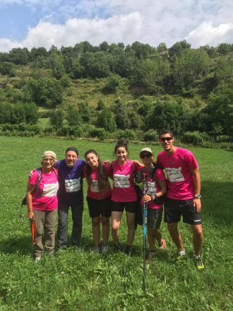 Grup del Projecte Vitamina a una prada dels Pirineus, porten samarretes del projecte i una noia porta bastons de muntanya