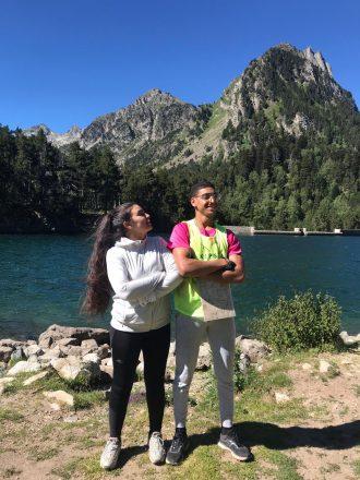 Un noi i una noia del projecte Vitamina als peus d'un embassament del Pirineu. Al fons es veu un pic escarpat, el noi porta un plànol penjat del coll