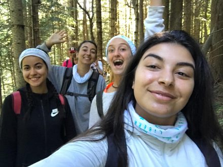 Quatre noies del projecte Vitamina caminat pel bosca, la fotografia es un selfie i les dues del darrera estan saludant a la càmera
