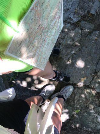 Primer plà picat on es veuen unes cames amb equipació per caminar per la muntanya. també es veu un plànol de situació penjat d'un cordill
