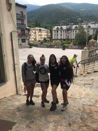 Quatre joves del projecte Vitamina posen juntes en una foto a un poble de muntanya, al fons es veu una plaça i una muntanya.